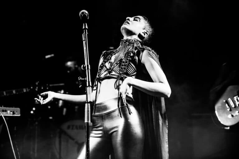 Black and white image of Juliana performing on stage, leaaning back with her hand on her hip and head pointing up up towards the ceiling