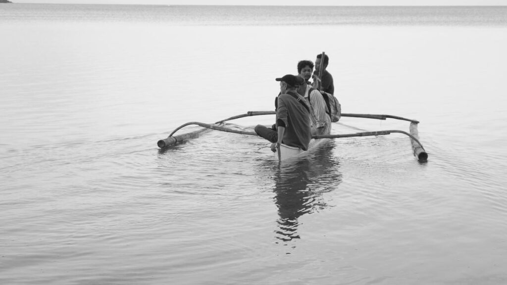 Three people on a rowing boat on water. Black and white image.