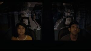Two people sit in the dark on an amusement park ride.