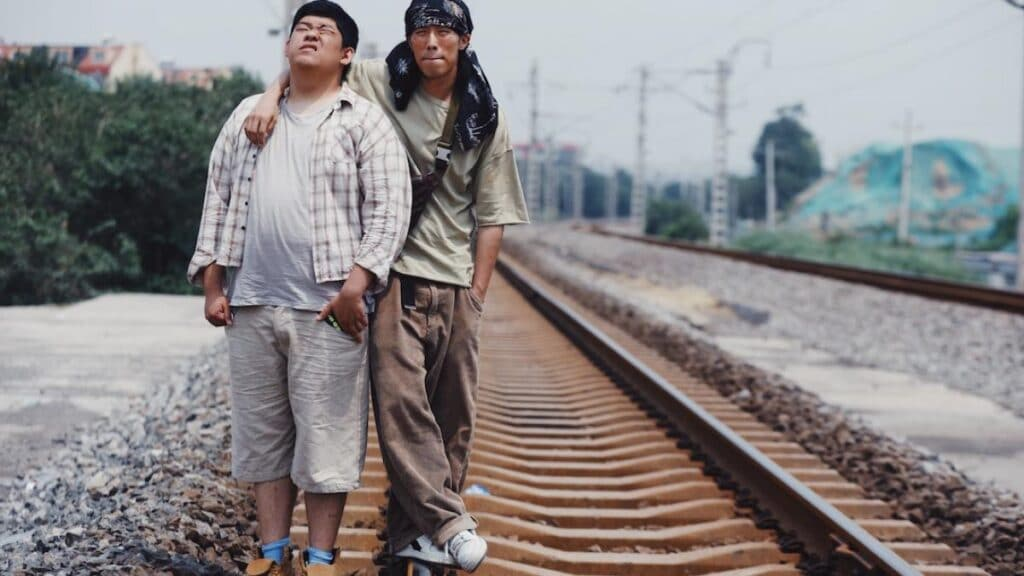 Two men standing next to train tracks