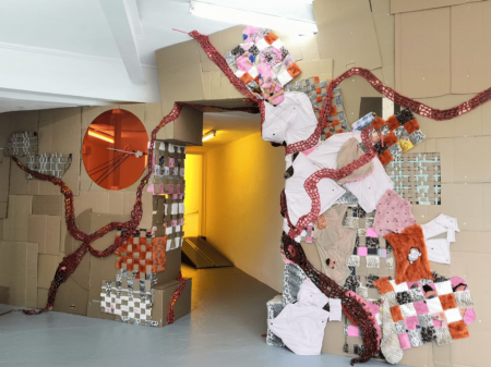 The inside of a gallery with a wall made of cardboard, stuffed animals and pink fabrics